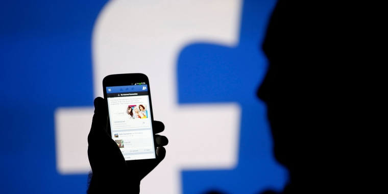 Image: A man uses the Facebook mobile app on a phone