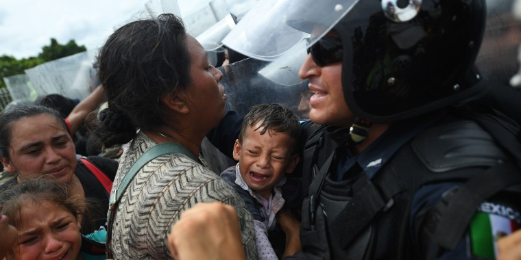 Honduran migrants heading in a caravan to the U.S., hold up a crying baby
