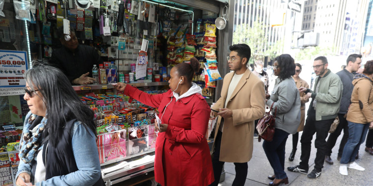 Image: FILE PHOTO: Customers line up to buy Mega Millions tickets at a newsstand in midtown Manhattan in New York