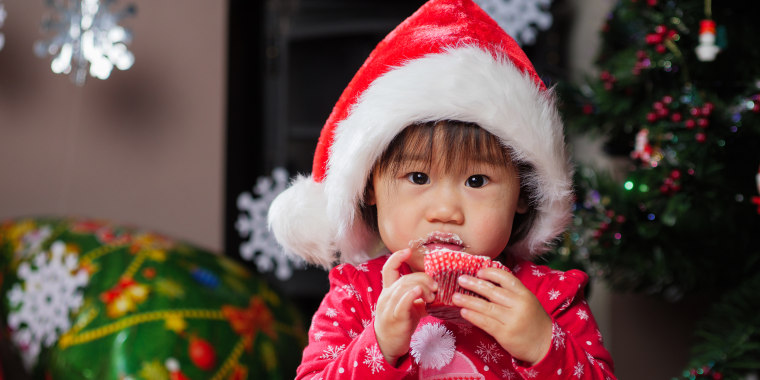 Close-Up Portrait Of Baby Girl Eating At Home During Christmas