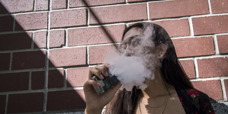 Image: An employee exhales vapor while using an electronic cigarette device