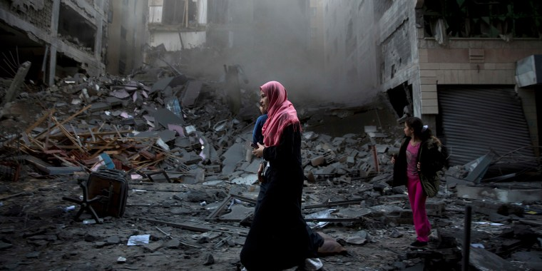Image: A Palestinian family walks next to a destroyed residential building hit by Israeli airstrikes in Gaza City