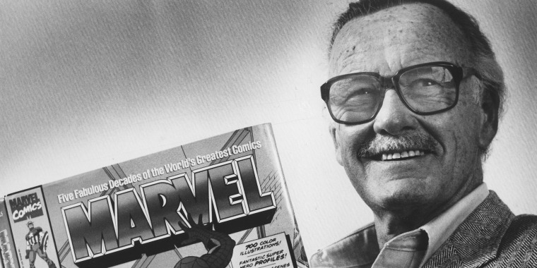 "Marvel Comics publisher Stan Lee poses with a book of ""Spider Man"" comics"