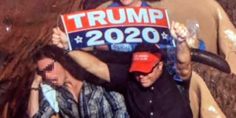 Dion Cini holds a Trump 2020 banner at Walt Disney World.