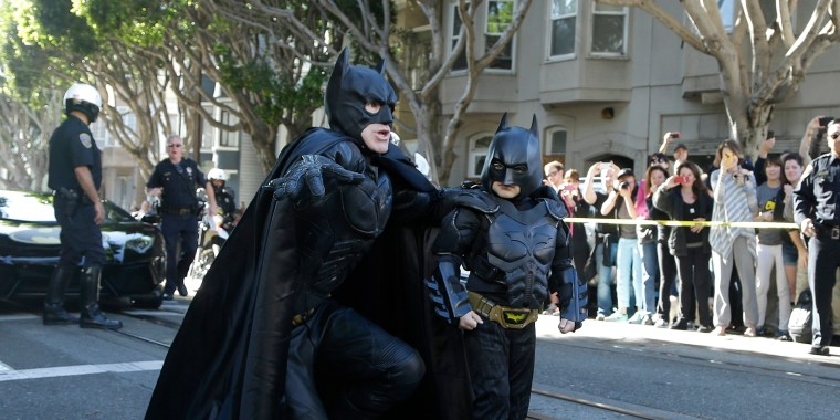 Miles Scott, dressed as Batkid, walks with Batman before saving a damsel in distress in San Francisco on Nov. 15, 2013.