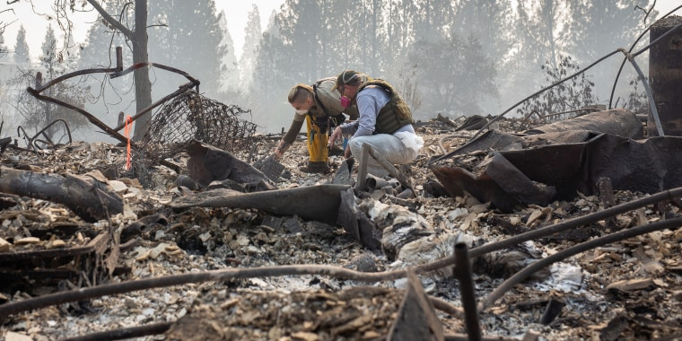 Search and rescue teams, often made up of volunteers, search for human remains among the debris of burned down homes on Nov. 16, 2018 in Paradise, California.