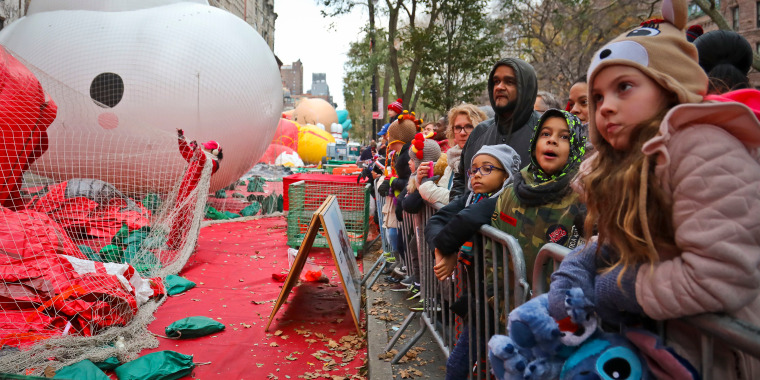 Image: Crowds gather to see giant character balloons being inflated the night before their appearance in the 92nd Macy's Thanksgiving Day parade