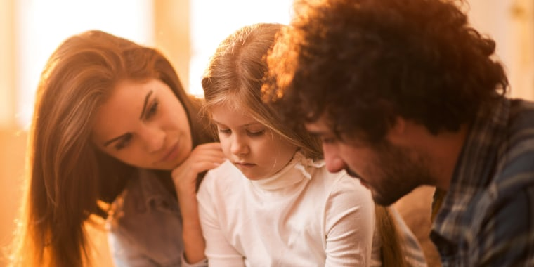 Image: Sad little girl at home being consoled by her parents.
