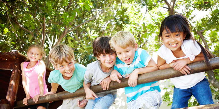Group of five kids hanging on a fence