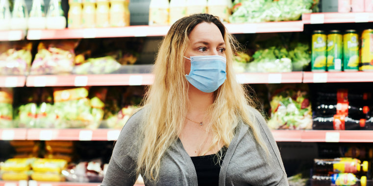 Woman buying food in grocery store, wearing medical mask