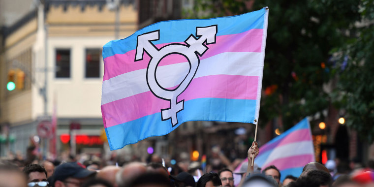 Image: A person holds a transgender pride flag as people gather on Christopher Street outside the Stonewall Inn for a rally to mark the 50th anniversary of the Stonewall Riots in New York.
