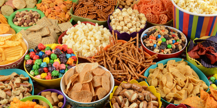 Full frame collage / variety of snacks in bowls; pretzels, popcorn, corn chips, crackers, peanuts, potato chips