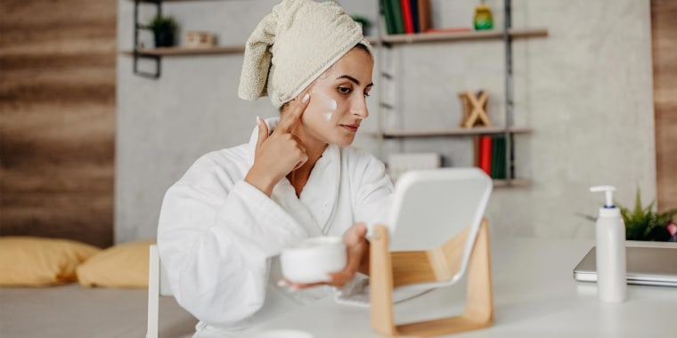 Woman rubbing lotion on her face to help with her rosacea