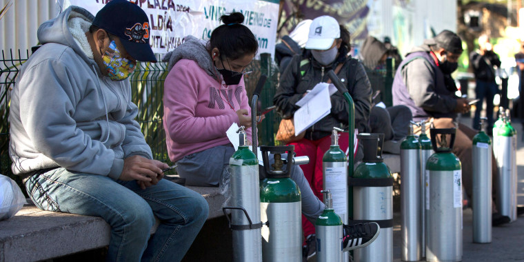 Image: People wait to refill oxygen tanks for relatives sick with COVID-19 in the Iztapalapa district of Mexico City