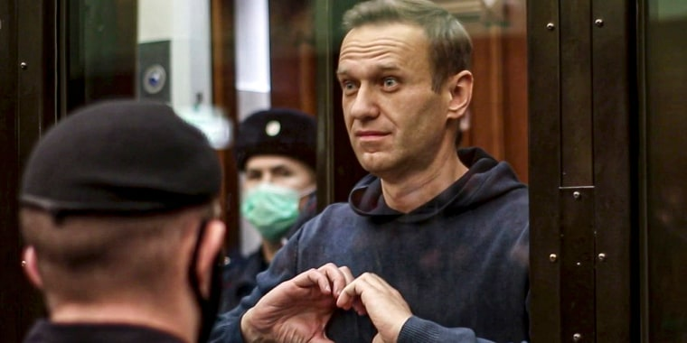 Image: Russian opposition leader Alexei Navalny shows a heard symbol standing in the cage during a hearing in the Moscow City Court,
