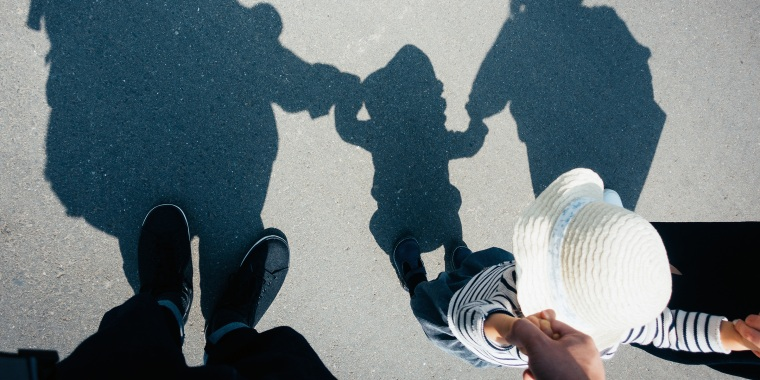 Shadow on gravel path of a loving family of three holding hands walking outdoors on a lovely sunny day
