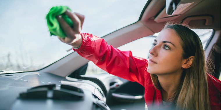Woman spring cleaning the inside of her car