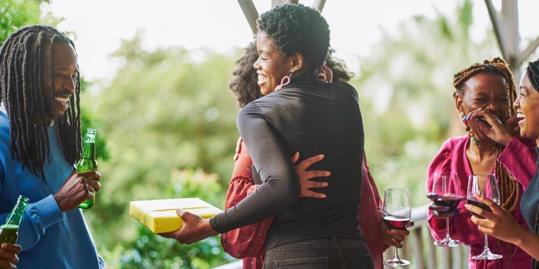 Sister-in-Laws hugging, after one got a gift wrapped in yellow wrapping paper