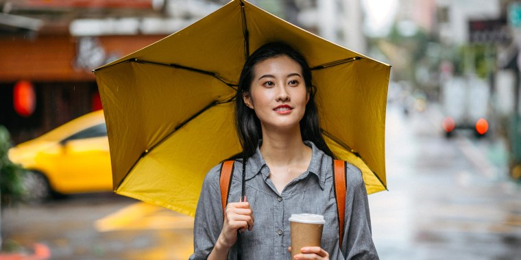 Woman walking outside with a cup of coffee, holding a yellow umbrella