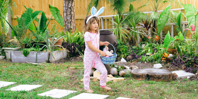 Little girl wearing Bunny ears and pj's, looking to fill her Easter basket
