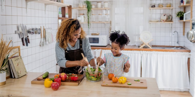 Mom and daughter in kitchen, chopping vegetables on their wooden kitchen island