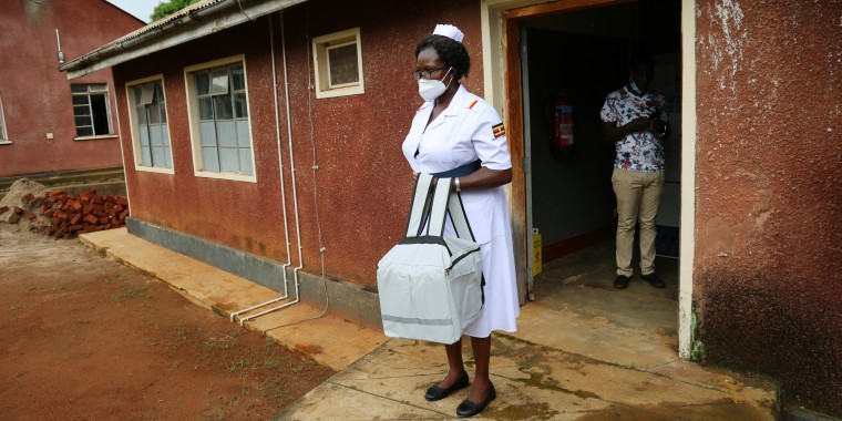 A nurse carries vaccine doses in a cool bag from a storage room located on Namatale Island, Lake Victoria, Uganda.