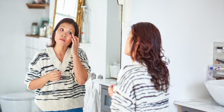 Woman looking in the mirror and touching her skin on her face