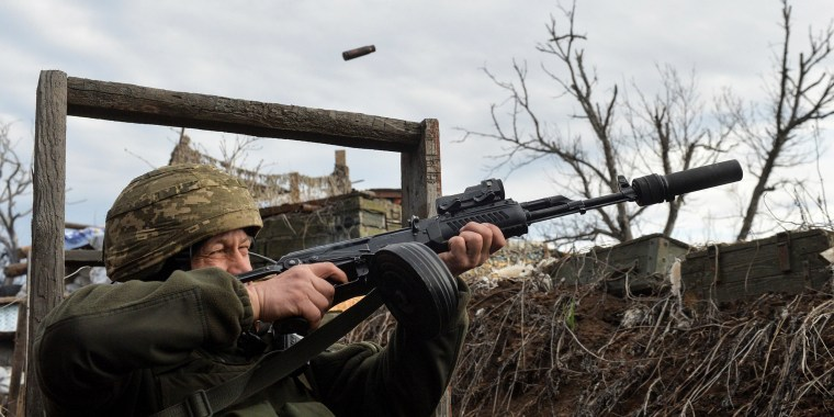 Image: A member of the Ukrainian armed forces fires in an attempt to shoot down an alleged unmanned aerial vehicle (UAV) at fighting positions on the line of separation from pro-Russian rebels near Donetsk, Ukraine