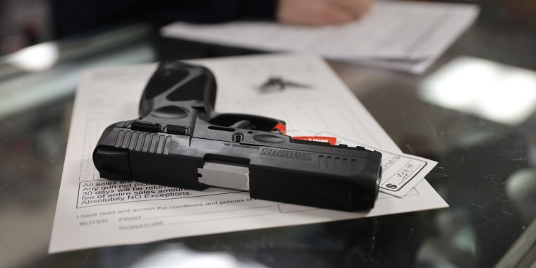 Image: A customer purchases a gun at Freddie Bear Sports on April 8, 2021 in Tinley Park, Illinois.