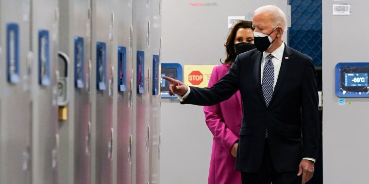 President Joe Biden and Michigan Gov. Gretchen Whitmer walk past freezers used to hold Pfizer-BioNtech Covid-19 vaccine as they tour a Pfizer manufacturing site on Feb. 19, 2021, in Portage, Mich.