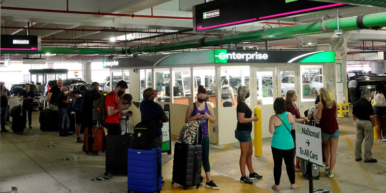 Image: People wait in line at Enterprise rental agency in the Miami International Airport Car Rental Center on April 12, 2021 in Miami.