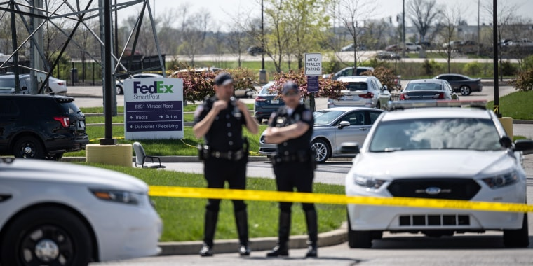 Image: Police officers stand behind caution tape near a crime scene on April 16, 2021 in Indianapolis.