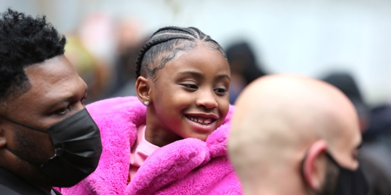 Gianna Floyd, daughter of George Floyd, wears a pink furry jacket as she is carried at a press conference outside a courthouse