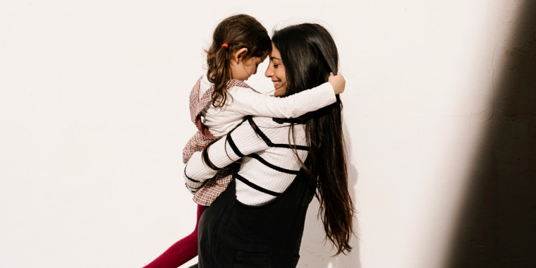 Affectionate mother and daughter against wall during sunny day