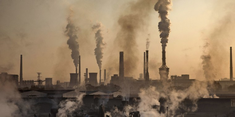 Image: Smoke billows from a large steel plant as a Chinese labourer works at a steel factory in Inner Mongolia, China.