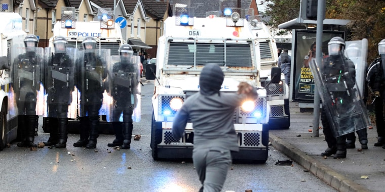 Image: A nationalist youth throws a rock at police officers in the Springfield Road area of Belfast