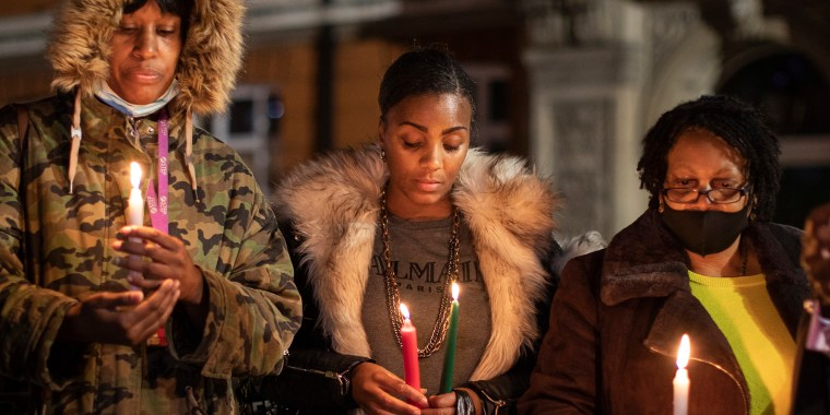 Image: A small group hold a candlelit vigil to mark what would have been the birthday of George Floyd, in Windrush Square in Brixton, London.