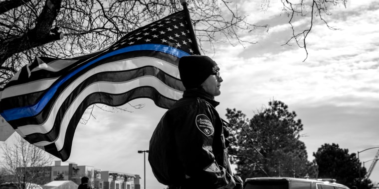 Image: A police officer with a Blue Lives Matter flag in a procession route during a memorial service.