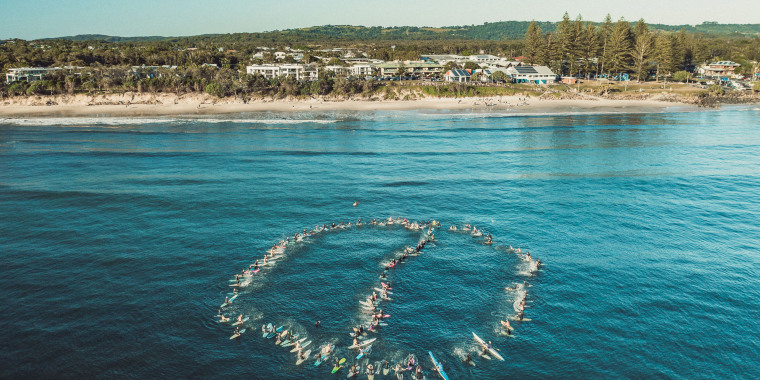 "Image: The ""paddle out\"" held by local surfers in Byron Bay, Australia."