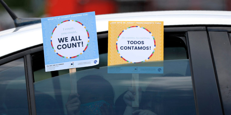 Image: Two young children hold signs through the car window that make reference to the 2020 U.S. Census as they wait in the car with their family at an outreach event in Dallas