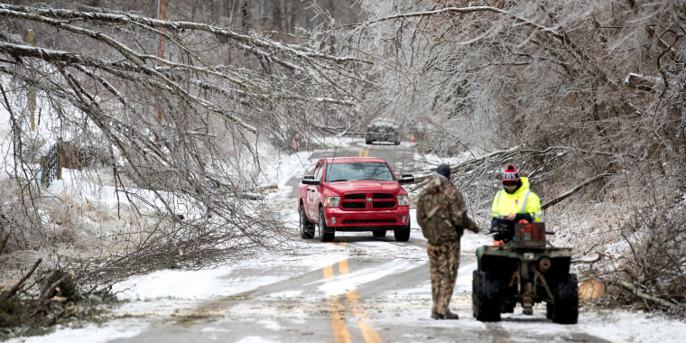 Vehicles navigate through downed trees along Blue Sulpher Road on Feb. 16, 2021
