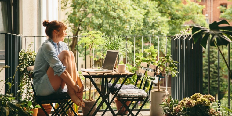 Smiling woman looking at her laptop on balcony