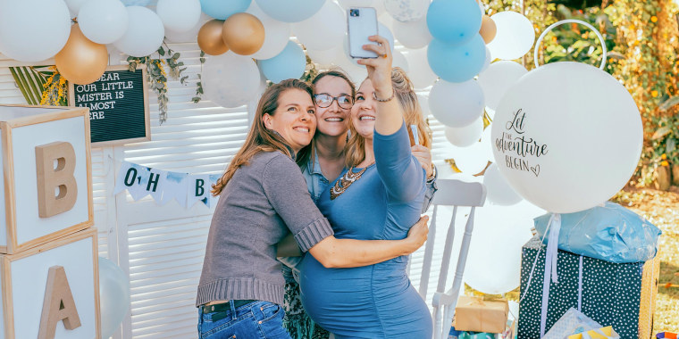 Three family members hugging at a baby shower
