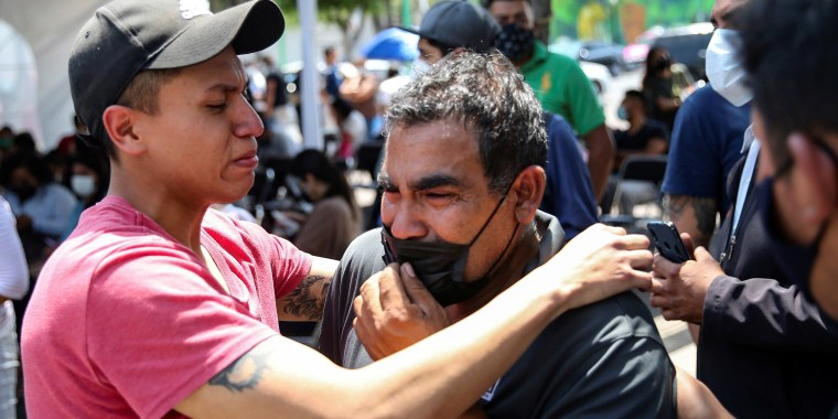 Image: Relatives of the victims react outside the Prosecutor's Office after an accident where an overpass of the metro partially collapsed with train cars on it, Mexico City