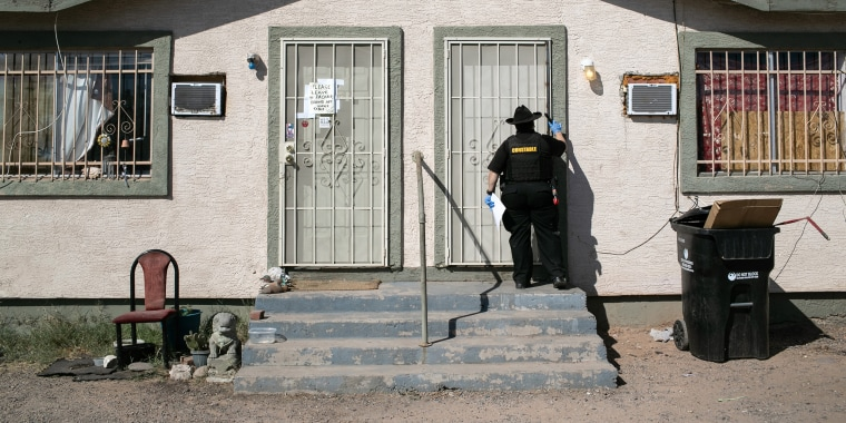 Image: A Maricopa County constable knocks on a door before posting an eviction order on Oct. 1, 2020 in Phoenix.