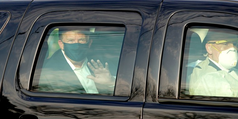 Image: President Trump waves from the back of a car in a motorcade outside of Walter Reed Medical Center in Bethesda, Md., on Oct. 4, 2020.
