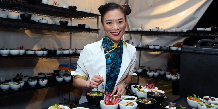 Shirley Chung smiles in a white jacket and blue Chinese-inspired blouse holding a fork over bowls of food
