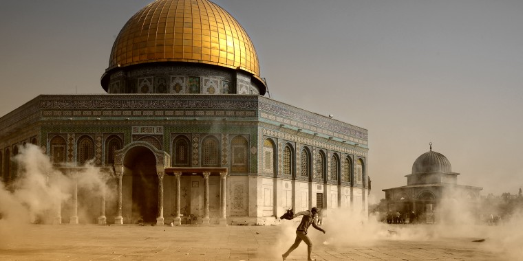 Image: A man runs away from tear gas at the Al Aqsa Mosque Compound.