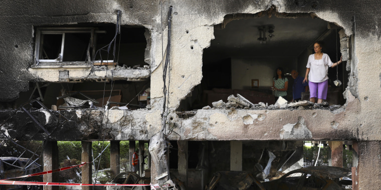 A member of Sror family inspect the rocket damage to their apartment in Petah Tikva, Israel, Thursday, May 13, 2021.