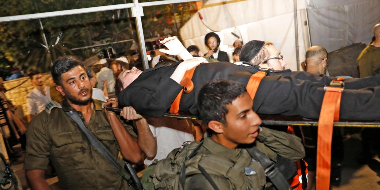 Members of Israeli security transport the injured following the collapse of bleachers at a synagogue in the Israeli settlement of Givat Zeev in the occupied West Bank on May 16, 2021.